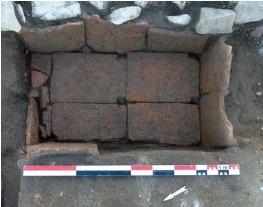 Vue de détail de l'auge en tuiles accolée au mur ouest d'un bâtiment.