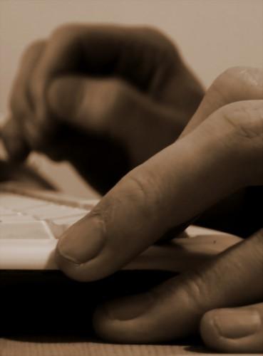 Mains sur un clavier, en sepia.