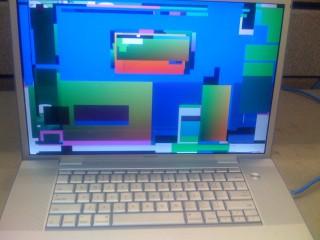 Photographie d'un écran d'ordinateur manifestement hors service, montrant des tâches de couleurs géométriques aléatoires