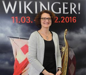 Archaeologist Dr. Michaela Helmbrecht in front of the exhibition's poster in Rosenheim