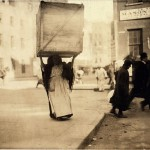 800px-Lewis_Hine,_Italian_woman_carrying_enormous_dry-goods_box,_New_York,_1912