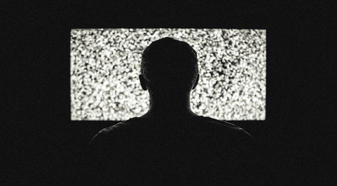 Homme devant une télévision