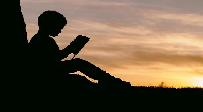 Silhouette d'enfant lisant au couché du soleil