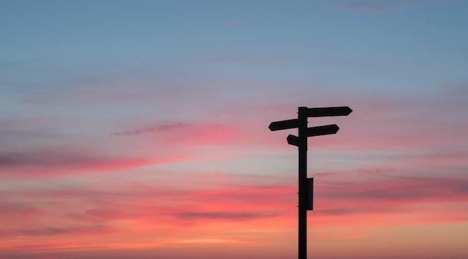 Panneau indiquant plusieurs directions dans le soleil couchant