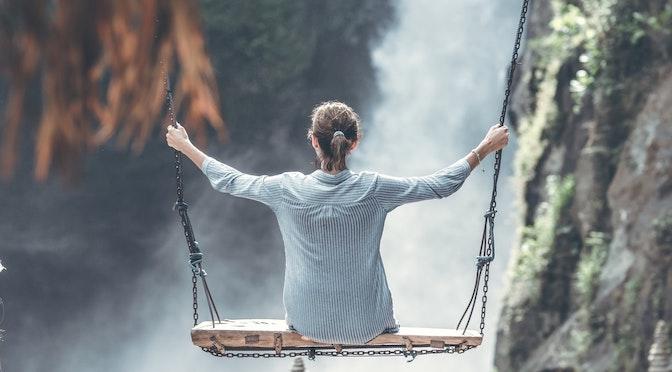 Jeune femme se balançant face à une chute d'eau