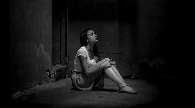 Jeune femme assise sur le sol dans le noir