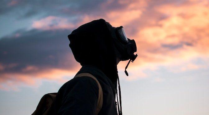 Personne portant un masque à gaz devant un ciel nuageux
