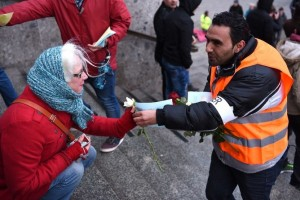 """Refugees from Syria present flowers to passers-by as they demonstrate against violence near the Cologne main train station in Cologne, western Germany on January 16, 2016, where hundreds of women were groped and robbed in a throng of mostly Arab and North African men during New Year's festivities. German authorities said that nearly all the suspects in a rash of New Year's Eve violence against women in Cologne were """"of foreign origin"""", as foreigners came under attack amid surging tensions. / AFP / PATRIK STOLLARZ"""