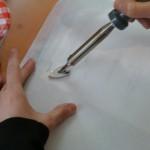 L'aplanissement des plis avec une spatule chauffante pour augmenter la lisibilité du document avant la numérisation.