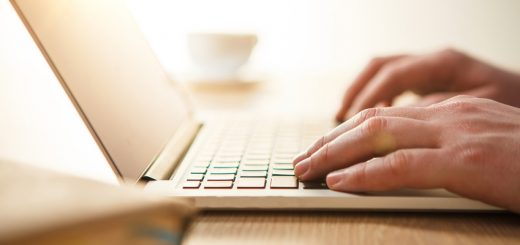 The male hands on the keyboard on the background of table