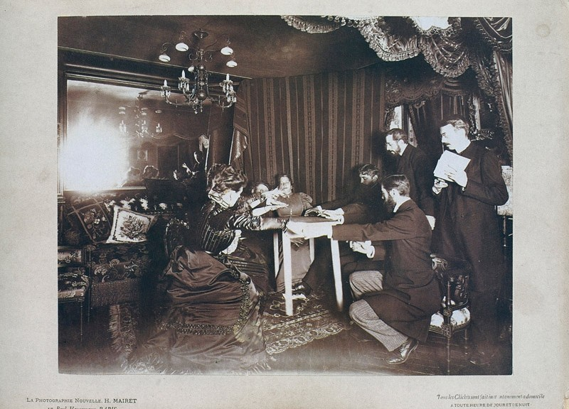 Le salon de Camille Flammarion lors d'une seance de spiritisme durant laquelle des personnes sont reunies autour d'une table les mains tendues au dessus de celle ci, a Paris en 1898. Au fond on apercoit la medium italienne Eusapia Palladino et a ses cotes (cache par les mains des autres) Camille Flammarion --- Camille Flammarion lounge in Paris in 1898 : spiritualism session with people around a table. In the background is italian medium Eusapia Palladino and near her (hidden by hands of the others) Camille Flammarion