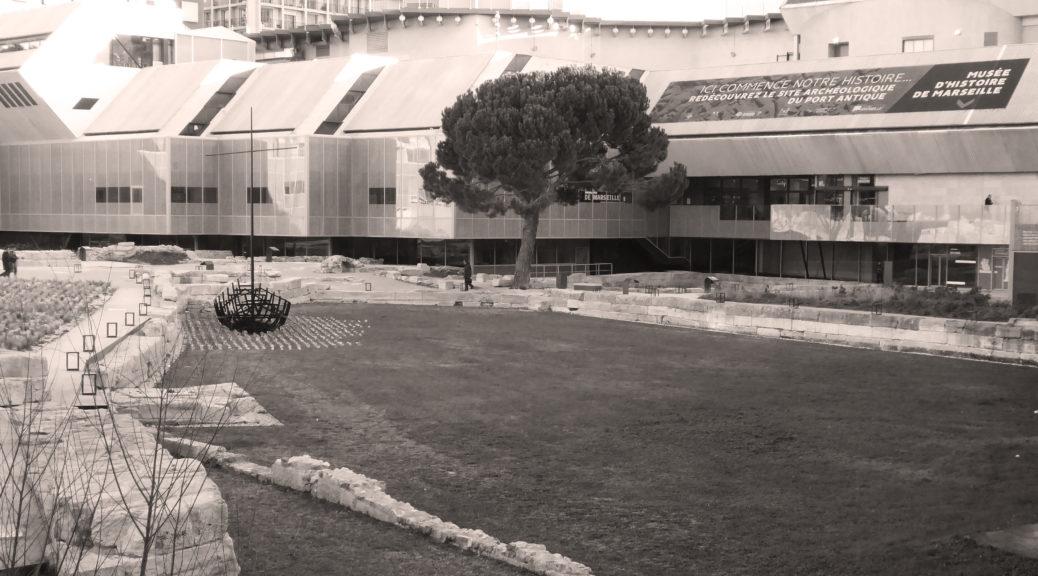 Vue du port antique et de l'entrée du musée d'histoire de Marseille au centre Bourse. Entre les ruines, a été installée une oeuvre représentant l'ossature d'un bâteau avec au sol des pierres bleues pour signifier la mer. On distingue à l'arrière plan le bâtiment du musée orné d'un pin parasol devant.