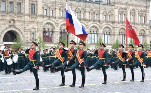 Soldaten in Paradeuniform marschieren mit einer russischen und einer sowjetischen Fahne