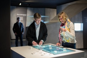 Besucher in der Dauerausstellung der Westfälischen Salzwelten: Der Medientisch ist ein interaktives Exponat auf dem man mit Spielsteinen aus fünf verschiedenen Kategorien kooperativ die Entwicklung eines Salinenbetriebs simulieren kann. Foto: Michael Bahr.