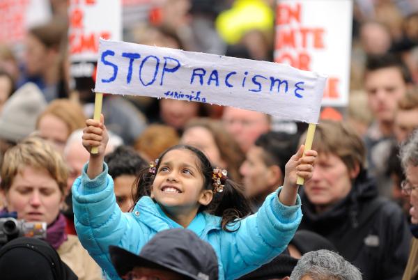 """Mädchen auf Demo hält Plakat mit """"stop racisme"""" Text"""