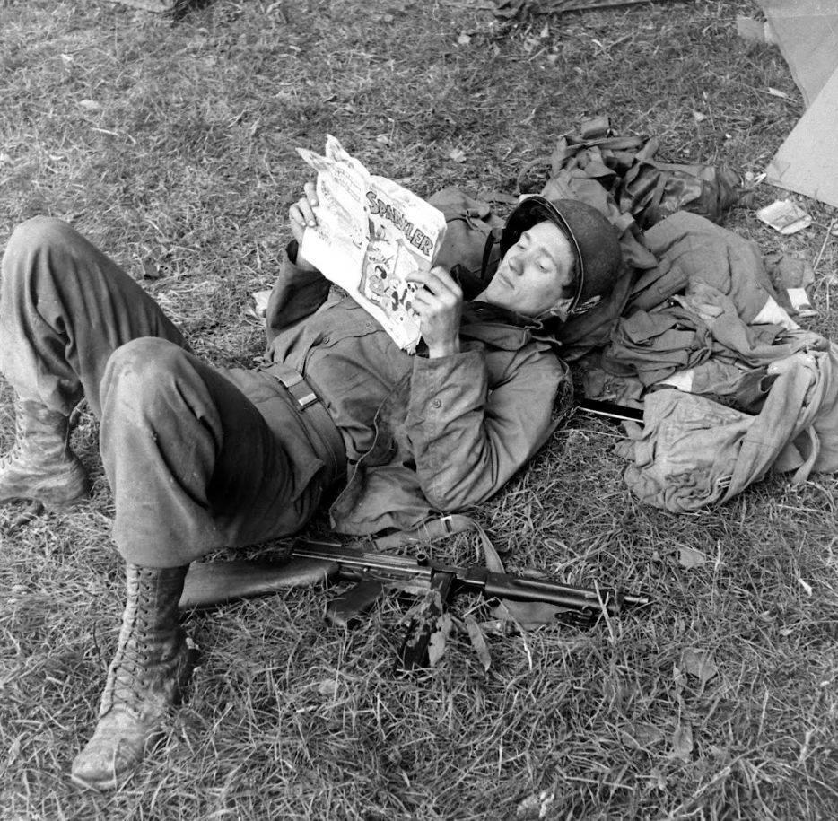 Carentan (Manche), entre le 15 et le 20 juin 1944. Allongé dans l'herbe près de sa tente, un parachutiste lit le numéro de juin 1944 de Sparkler Comics. Réf. LC001826. Life Photo Collection via Google Cultural Institute.