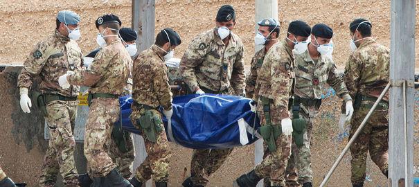 des-soldats-italiens-transportent-le-corps-d-un-migrant-repeche-au-large-de-l-ile-de-lampedusa-le-7-octobre-2013_4114398