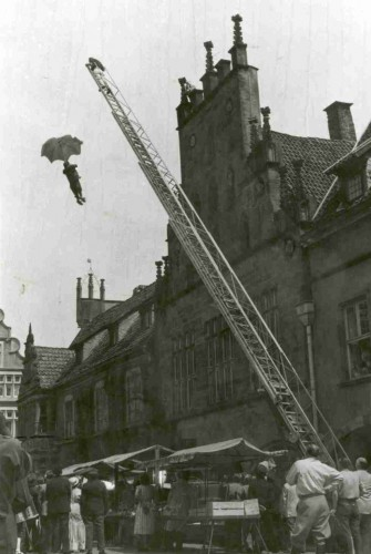 """Filmaufnahmen """"Der tolle Bomberg"""" 1957 auf dem Lemgoer Marktplatz - Feuerwehrleiter mit Puppe (Double)"""