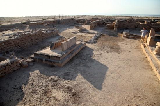Figure 4: Secteur des temples, surcreusé. De gauche à droite: rempart, autel, templeA; derrière le personnage, templeB. Vue vers le sud. ©MAFKF.