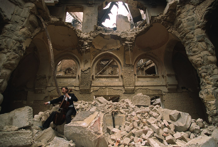 Cellist Vedran Smailović playing in the ruins of the National Library at Sarajevo. Photograph by Mikhail Evstafiev.