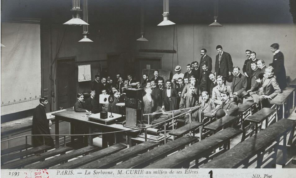 Carte postale du début du 20e siècle représentant Pierre Curie au milieu de ses élèves. Cote : BIS, Réserve, RBA 3= 163-2 Pièce 6