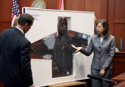 Amy Siewert, a firearms expert with the Florida Department of Law Enforcement, faces the jury as shows Trayvon Martin's hooded sweatshirt in Seminole circuit court, in Sanford, Fla., Wednesday, July 3, 2013. Zimmerman is charged with second-degree murder in the fatal shooting of Trayvon Martin, an unarmed teen, in 2012. (AP Photo/Orlando Sentinel, Jacob Langston, Pool)