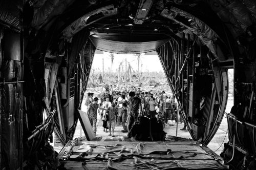 EASTERN SAMAR, PHILIPPINES -  Evcauees board a military plane offering free transport from affected areas December 7, 2013. DISPLACED EARTH/SIGNOS SERIES 2009 - 2015 Photograph by Veejay Villafranca
