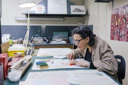 Maria d'Ajuda Santana, restauratrice au département de la Musique nettoie et replace les échantillons de tissus agrafés sur les 21 dessins des maquettes des costumes conçus en 1916 pour l'opéra Madame Sans-Gêne des collections de la Bibliothèque-musée de l'opéra. (c) Guillaume Murat/BnF