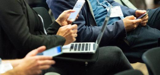Verschiedene Personen sitzen bei einer Diskussionsveranstaltung und haben alle ihre Handys in der Hand.