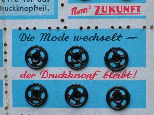 """Die Mode wechselt – der Druckknopf bleibt! Pryms Zukunft"" 7mm-Metaldruckknöpfe, Fa. Prym, 2. Hälfte 20. Jh. © Museumsquartier Osnabrück, A 5596"