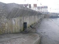 Mur antichar d'Arromanches (Calvados). L'ancienne cale des pêcheurs du petit village d'Arromanches offrait une véritable brèche dans le système défensif allemand. Pour bloquer l'accès au village depuis la plage, un large mur antichar fut construit. Haute de plus de 3 mètres, cette muraille était surmontée d'une rangée de barbelés. De nos jours, ce mur existe toujours et fait office de digue, mais passe presque inaperçu. (B. Labbey/CRHQ)