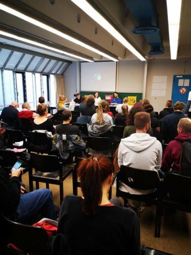 Auf diesem Foto sieht man die Rückenansicht von Menschen, die auf Stühlen sitzen und vorne zu den Referenten blicken.