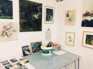 Ausstellungsansicht mit Zeichnungen und Gemälden an den Wänden außerdem ein Glastisch mit Flyerrn
