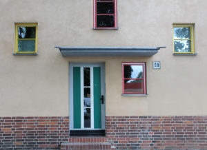 Ein grüne Tür mit vertikal verlaufenden Fenstern in der Mitte, die mit einer Stufe in ein Wohnhaus führt