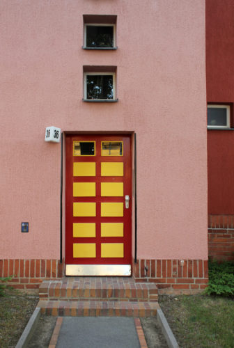 Eine Tür in rot und gelb, die mehrfach gegliedert ist und in ein rosanes Haus führt