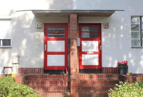 Zwei rot-weiße Türen, die horizontal in drei Teile gegliedert sind, wobei das oberste Drittel aus Glas besteht und mit drei Stufen in ein weißes Wohnhaus führen