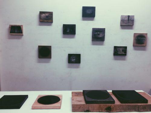 Ausstellungsansicht mit kleinformatigen Werken an der Wand und einem Tisch im Vordergrund
