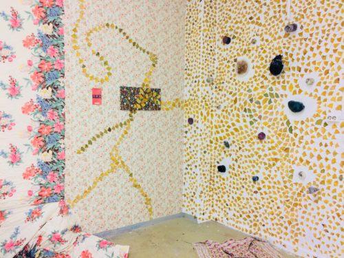 Bunte Wandinstallation aus Tapenten und gelben Punkten die sich um Steine gruppieren
