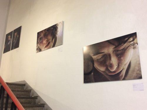 Drei Fotografien neben einer Treppe. Die Werke zeigen das Gesicht einer jungen Frau