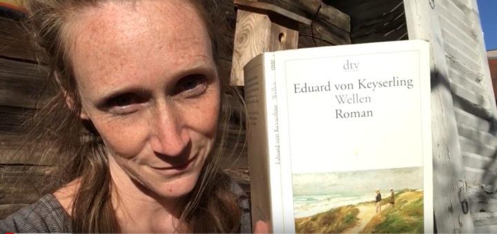 """Eine rothaarige Frau sitzt draußen vor einer Holzhütte und hält den Roman """"Wellen"""" von Eduard von Keylering in die Kamera. Es handelt sich um einen Screenshot von Youtube."""