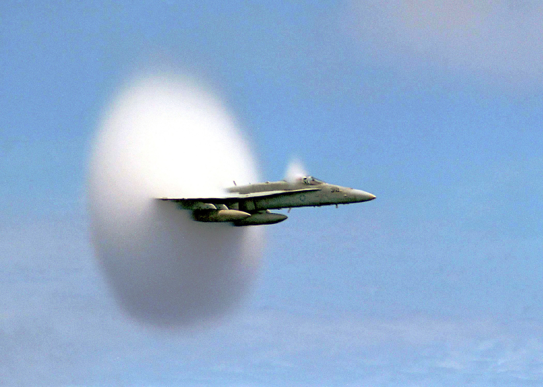 """990707-N-6483G-001 ABOARD USS CONSTELLATION (July 7, 1999)-- Lieutenant Ron Candiloro, assigned to Fighter Squadron One Five One (VF-151), breaks the sound barrier in an F/A-18 """"Hornet"""". VF-151 is currently deployed with the USS Constellation (CV 64) battlegroup.  U.S. Navy photo by Ensign John Gay.  (RELEASED)"""
