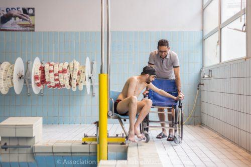 Personne en situation d'handicap sortant d'une piscine. Photo.