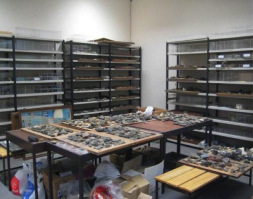 imagem em que se vê uma mesa de trabalho com vários objectos e prateleiras