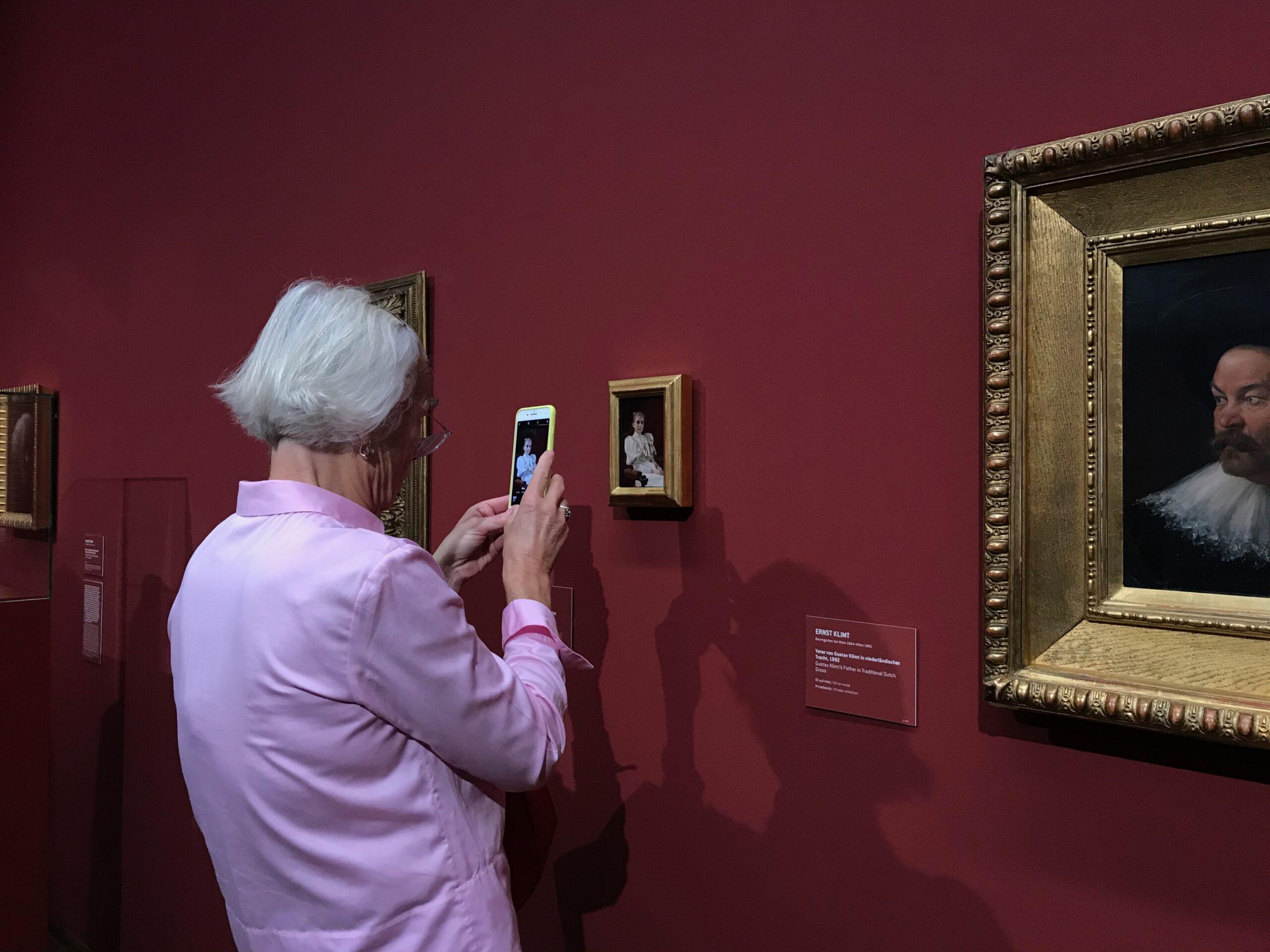 Na imagem vê-se uma mulher a tirar uma foto com o seu smartphone a uma pintura num museu