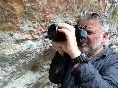 Film director Guy Beauché in front of hand-stencils in Kundumbu rockshelter.