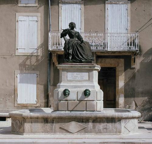 Grignan. Place de la Fontaine, fontaine monumentale. Le pilier central sert de piédestal à la statue de Madame de Sévigné, érigée en 1857.