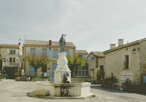 Montjoyer. La place du village, avec au centre la fontaine surmontée d'une statue de Saint-Paulin.