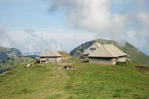 Seythenex (Haute-Savoie). Vue d'ensemble des Chalets de l'Aulp (1 720 m), avec la cave formant un tertre en arrière-plan (Caroline Guibaud © Région Rhône-Alpes, Inventaire général du patrimoine culturel / Parc naturel régional du Massif des Bauges, 2010 - ADAGP)