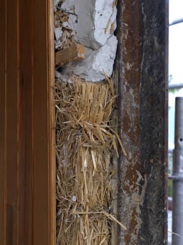 """Détail d'un mur de façade au droit d'un pilier métallique : lambris de pin, liteau, panneau de paille compressée (""""solomite"""") calé au plâtre."""
