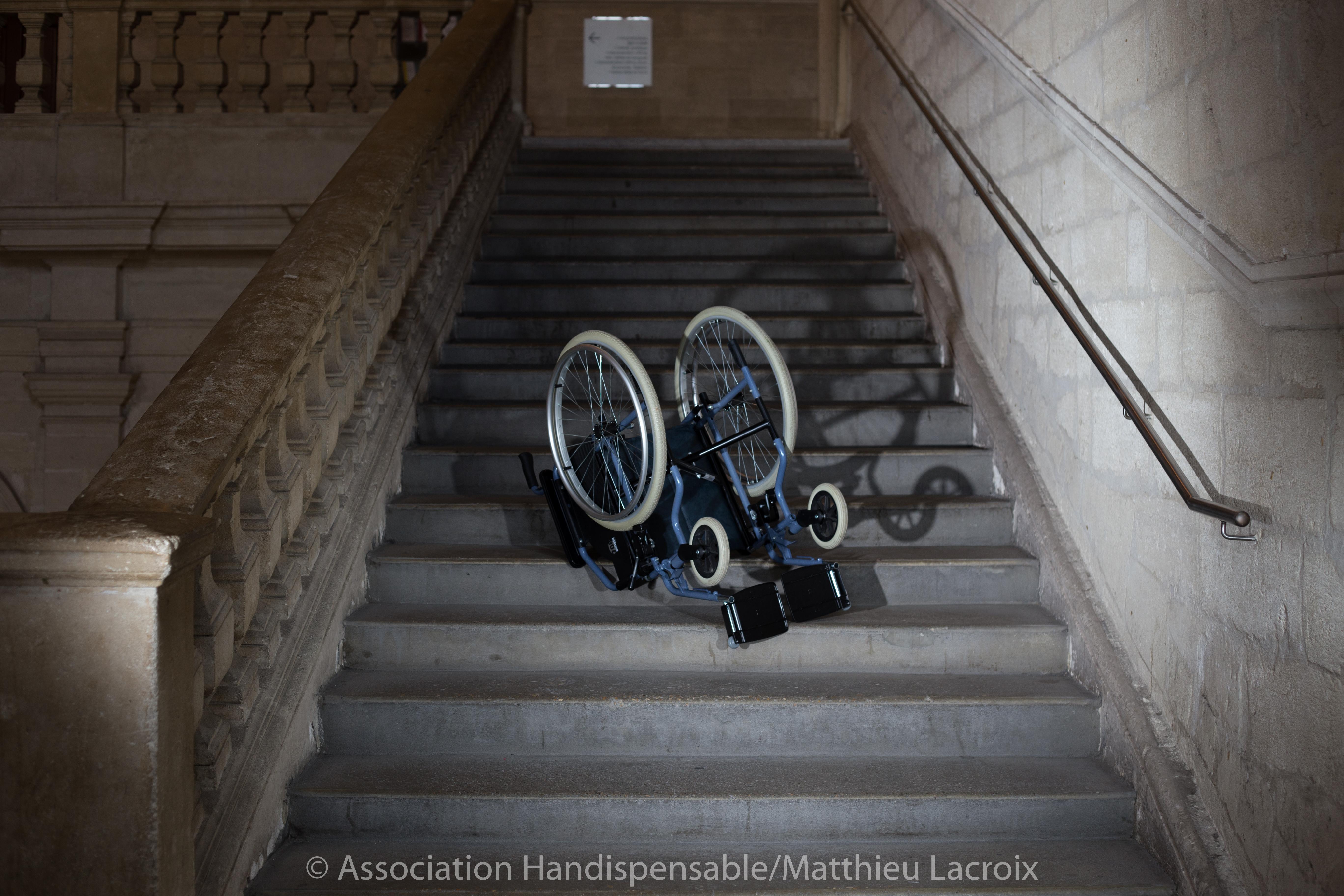 Photographie d'un fauteuil roulant renversé dans les escaliers. Illustre les problèmes d'accessibilité.